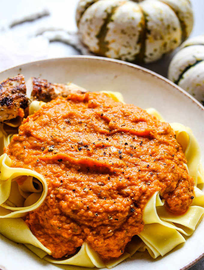 Creamy pumpkin harvest pasta sauce coats thick cut pasta noodles and is topped with freshly cracked pepper.