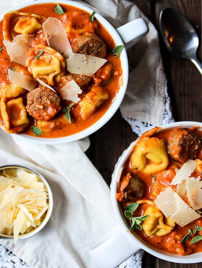 tortellini and sausage creamy tomato soup with a second bowl filled to the rim and a small cup of shaved parmesan cheese for delicious toppings.