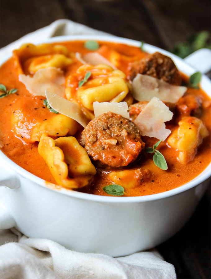 tortellini and sausage creamy tomato soup has slices of pan seared sausage, tortellinis, shaved parmesan and fresh thyme.