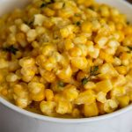 Creamed corn with parmesan is topped with fresh thyme to add color, texture, and flavor.