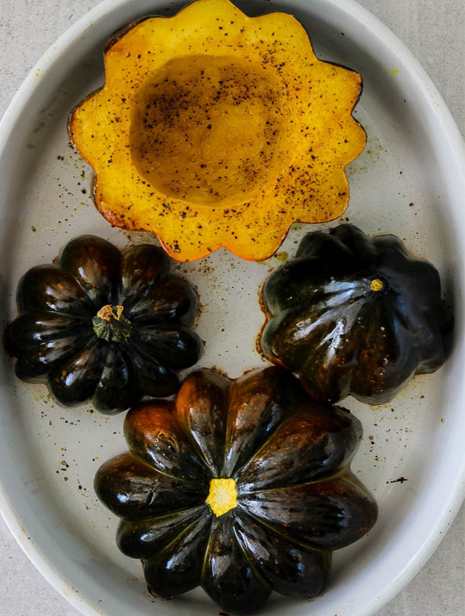 Acorn squash are halved, greased on the inside with olive oil, salted, and layed cut side down in a dish to prepare for baking.