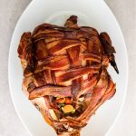 Bacon wrapped turkey breasts is fully cooked with crunchy bacon and stuffed with carrots, celery, onion, and herbs.