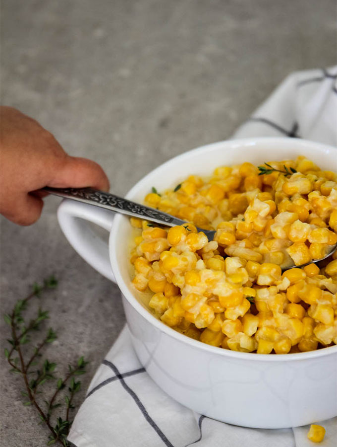 Creamed corn is plated in a white bowl and topped with fresh garden picked thyme.