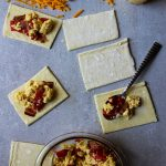 Bacon, egg and cheese pop tarts are assembled by cutting squares in the dough, topping with the scrambled egg mixture, then topping with another square of dough.