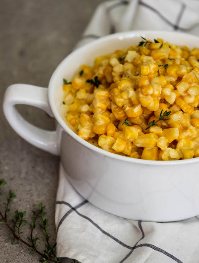 Creamed corn is served with fresh thyme for a fresh pop of color and flavor.