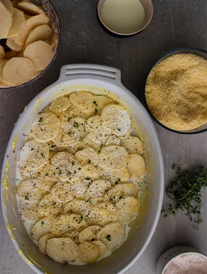 Potato au gratin is assembled by scalloping the potatoes, layering them in a single layer, and adding milk, cheese, and herbs.