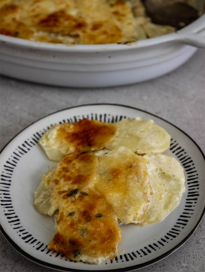 Potato au gratin is served on a plate to show cheesy and silky texture.