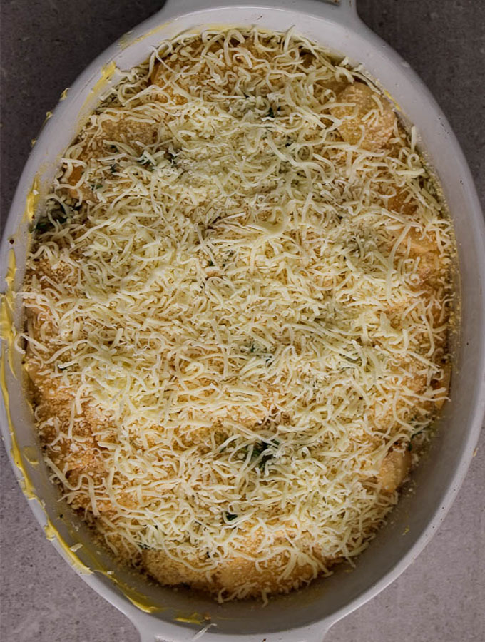 Potato au gratin is finished off by covering the top layer with cheese before baking it.
