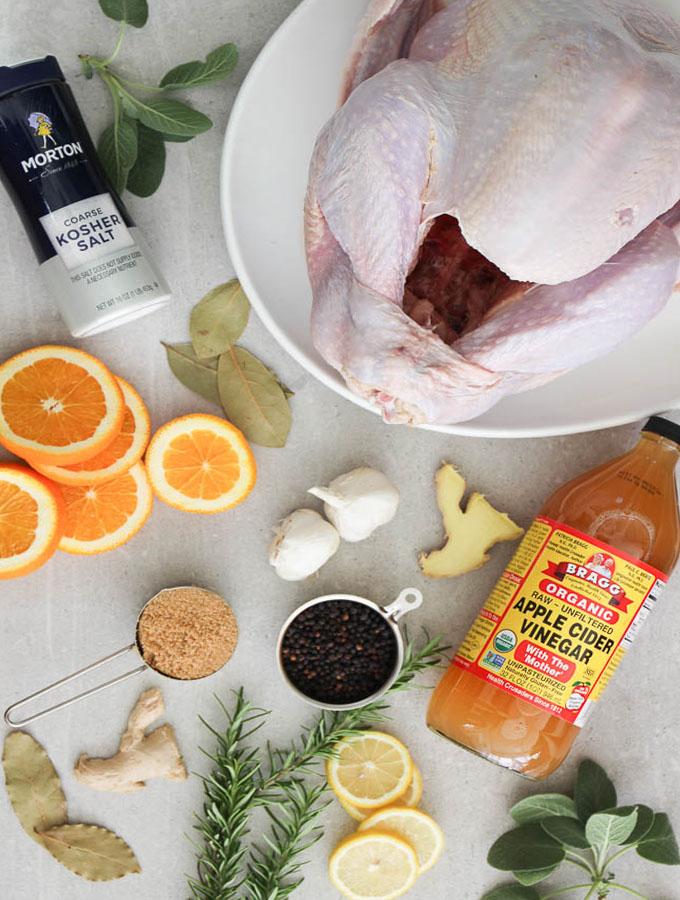 Turkey brine ingredients include salt, peppercorns, apple cider vinegar, bay eaves, ginger, garlic, sage, and brown sugar.