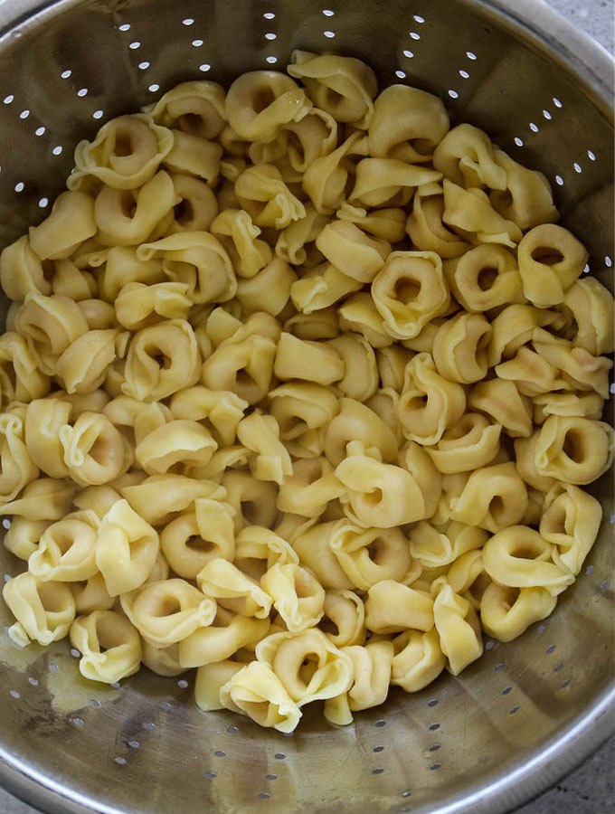 Tortellinis are drained in a strainer before being tossed with green goddess dressing.