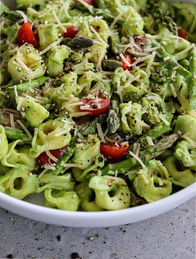 Green Goddess Tortellini Salad is mixed together and topped with parmesan cheese and plated in a white bowl.