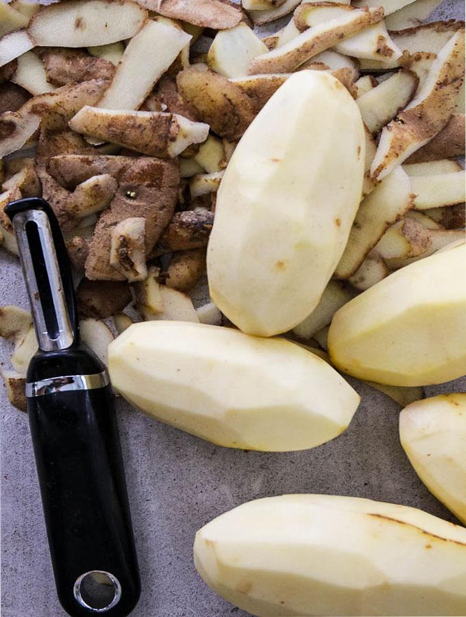 Potato latkes begin with peeling the russet potatoes.