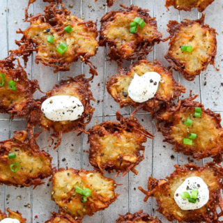 Potato latkes are on a cooling rack and are topped with sour cream, chives, and cracked pepper.