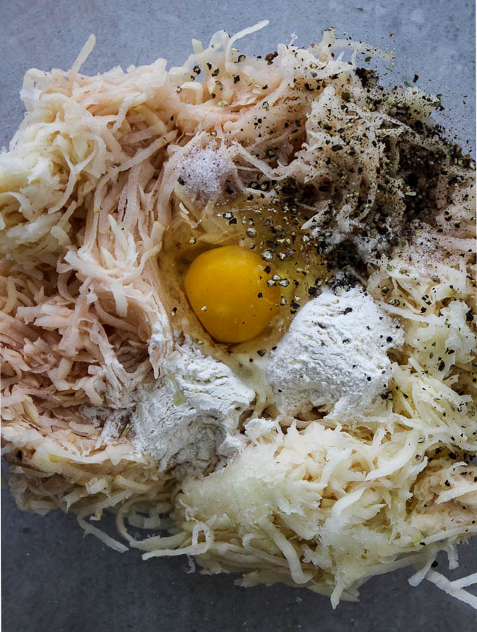 Potato latke recipe calls for shredded potato, grated onion, an egg, flour, and salt and pepper.