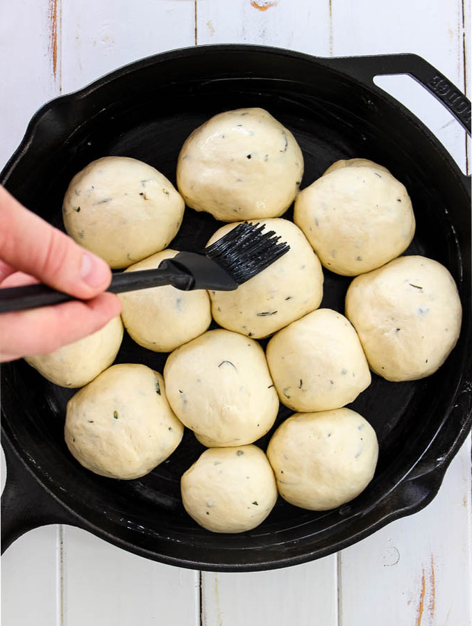 An egg wash is brushed on top of the Rosemary Garlic Dinner Rolls inside a cast iron pan.