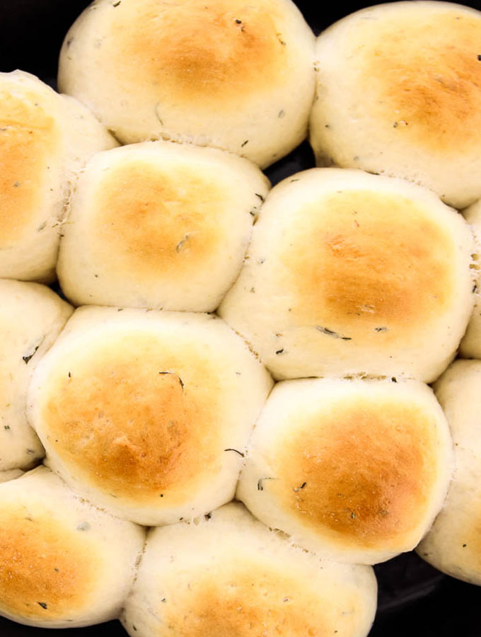rosemary garlic bread rolls made in a cast iron are perfectly browned on the top.