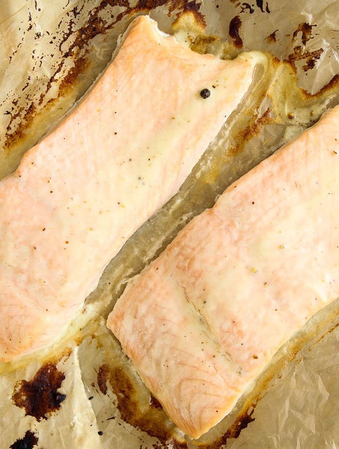 Salmon filets are coated with lemon juice, olive oil and garlic, then baked on a baking sheet.