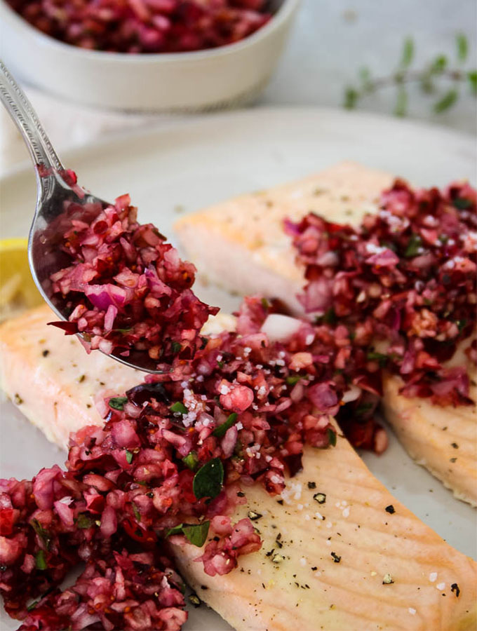 Salmon with Cranberry Relish is plated with heaps of relish on top of the salmon and a spoonful of it.