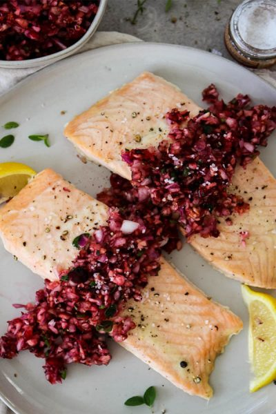 Salmon with Cranberry Relish is plated with heaps of relish on top of the salmon, wedges of lemon for added color, and course salt.