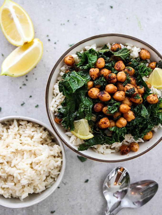 Smoky Chickpea and Kale Rice bowl is plated in a white bowl with a side bowl of rice, a couple of spoons, and wedges of lemon for added color and zest.