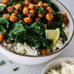Smoky chickpea and kale rice bowl is plated in a white bowl and topped with small wedges of lemon for added color.