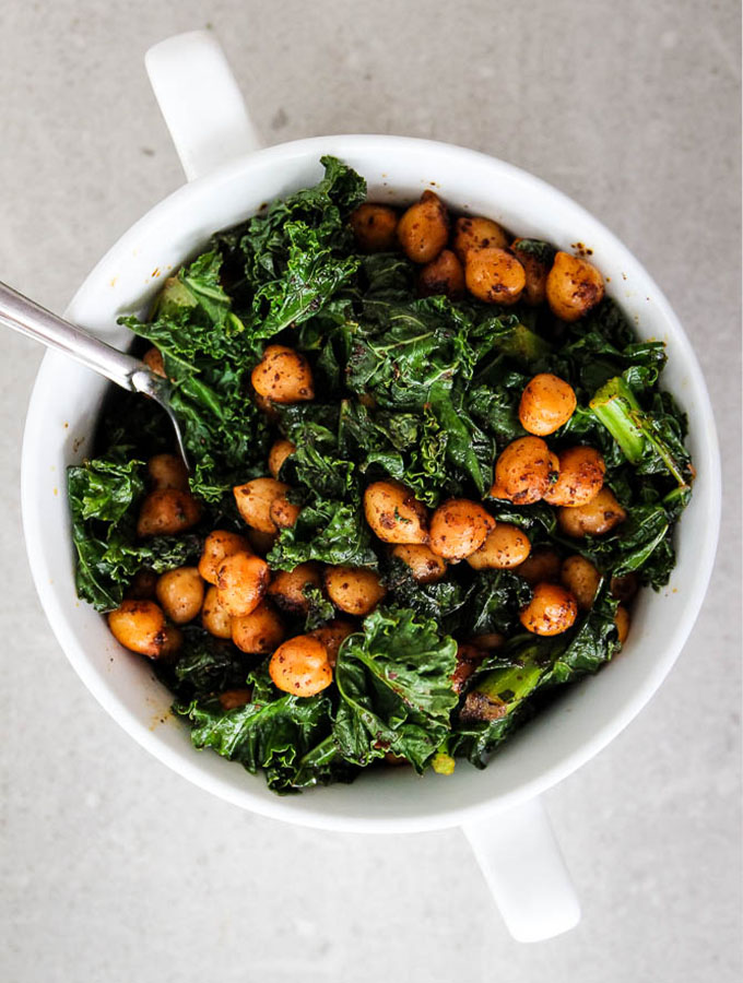 Smoky chickpea and kale rice bowl is plated in a white bowl with a spoon to show color and texture.