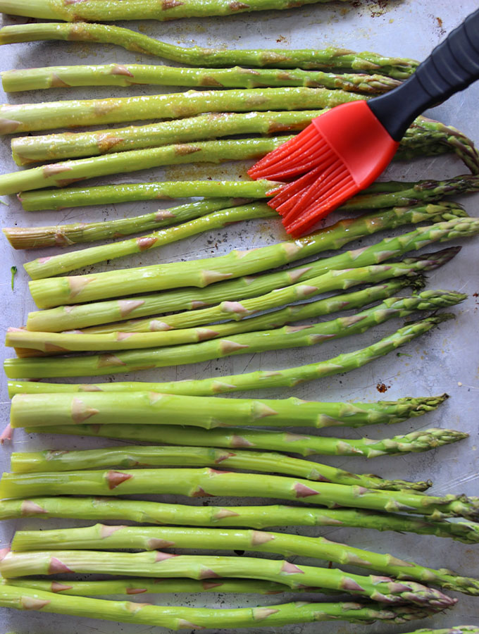 Asparagus is brushed with a basting brush to apply olive oil before roasting.