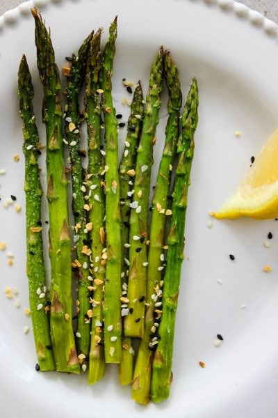 Asparagus is served on a white plate with lemon, and sprinkled with Trader Joe's Everything Bagel seasoning.