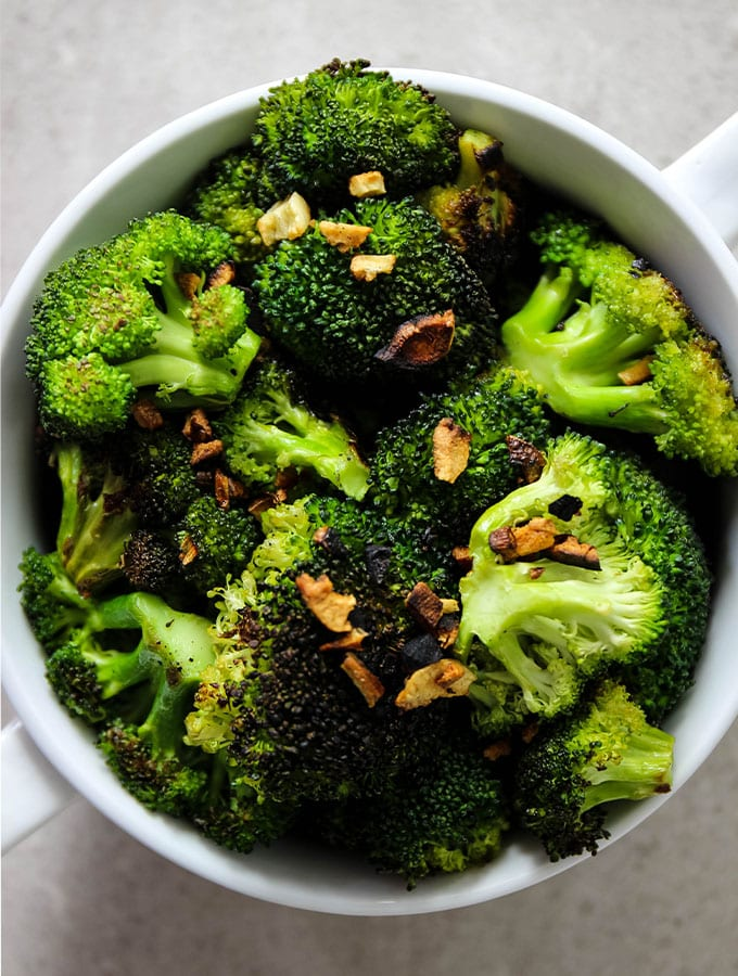 Pan roasted broccoli with garlic is plated in a white bowl and topped with the little bits of browned garlic.