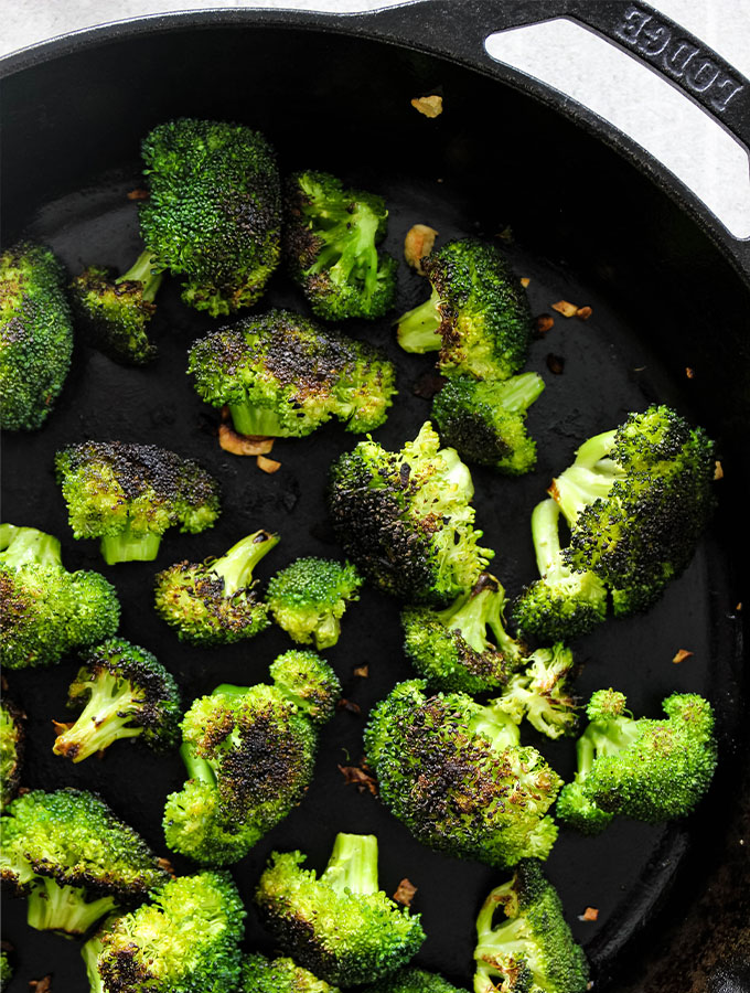 Broccoli is roasted to browned perfection in a cast iron pan.