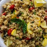 Quinoa salad is plated in a white bowl with a side of lemons and more fresh basil for added color and flavor.