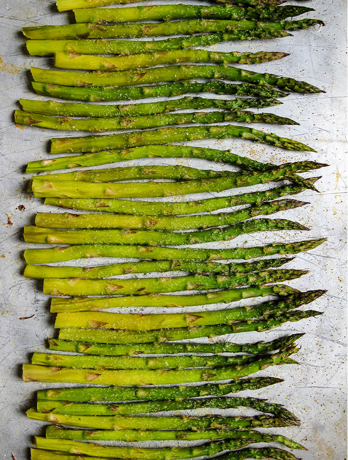 Asparagus is placed in a single layer on a baking sheet in preparation to roast.