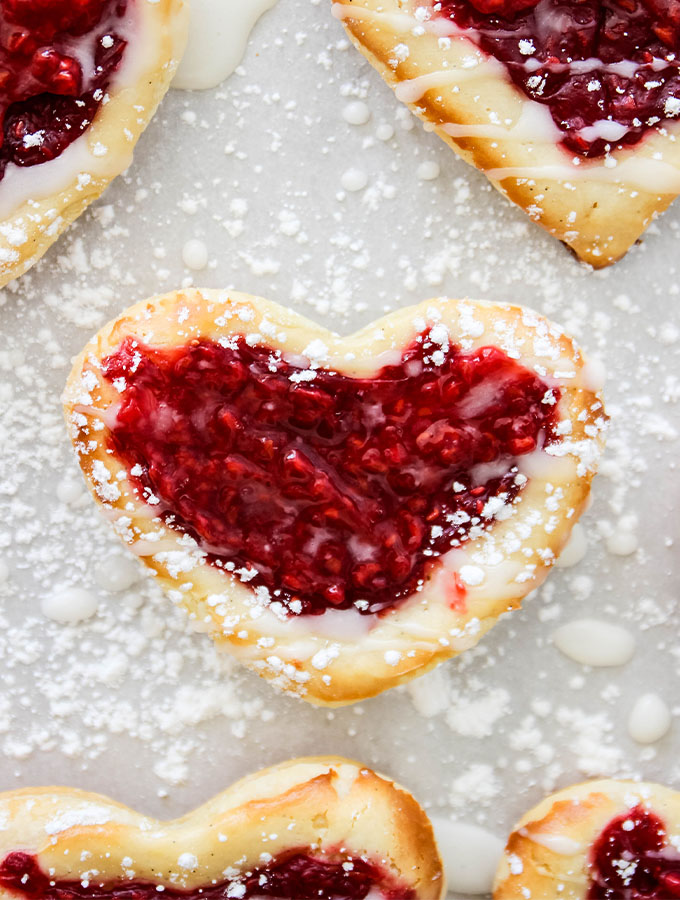 Easy raspberry cream cheese puff pastry danish are frosted with an almond icing and served with sprinkled confectionary sugar.
