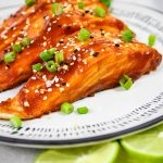 Sriracha Honey Baked Salmon is plated and topped with chives.