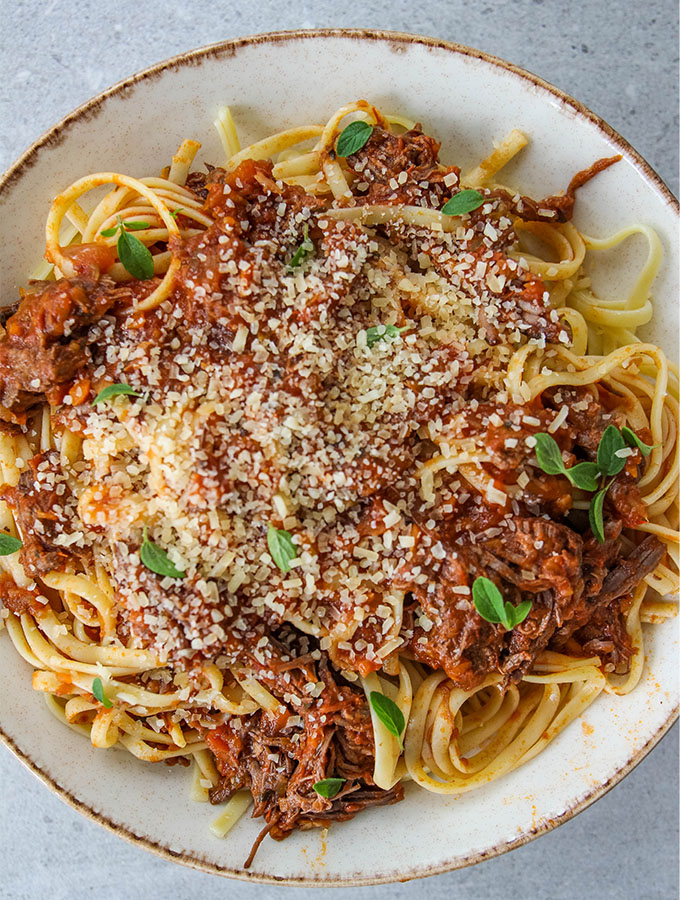 Instant Pot Beef Ragu Pasta is plated and sprinkled with cheese and fresh herbs.