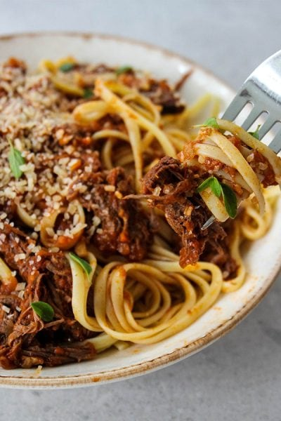 Instant Pot Beef Ragu Pasta is plated in a bowl, topped with cheese and fresh herbs.