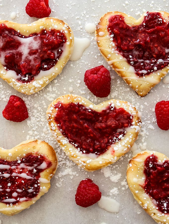 raspberry cream cheese puff pastry danish is frosted with icing and sprinkled with confectionary sugar.