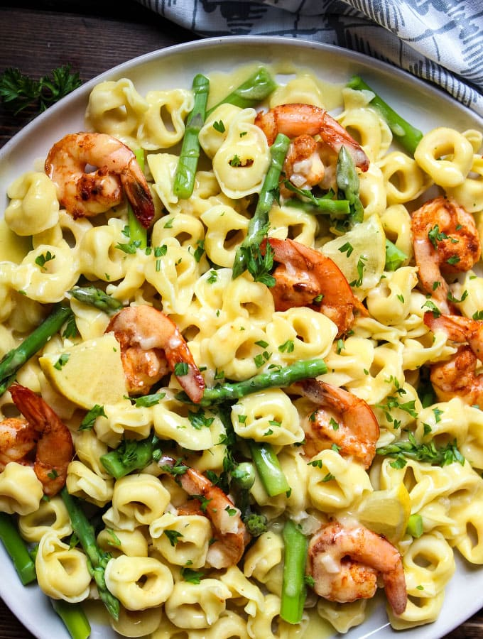 Shrimp and Tortellini with Beurre Blanc is plated in a white dish and topped with parsley.
