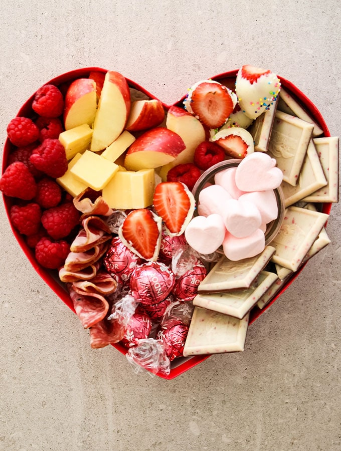 Apples, raspberries strawberries, cheese, salami and valentine's day themed candies are inside of a heart shaped box for a valentine's day charcuterie board.