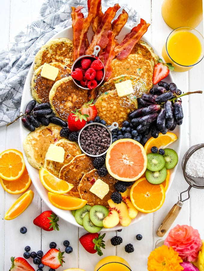 Pancake breafast board is displayed across a table with fresh orange juice and powdered sugar.