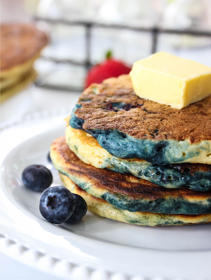 Buttermilk pancakes are staked, topped with butter and topped with fruit.