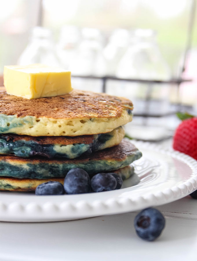 Buttermilk pancakes are stacked and topped with butter and fresh fruit.