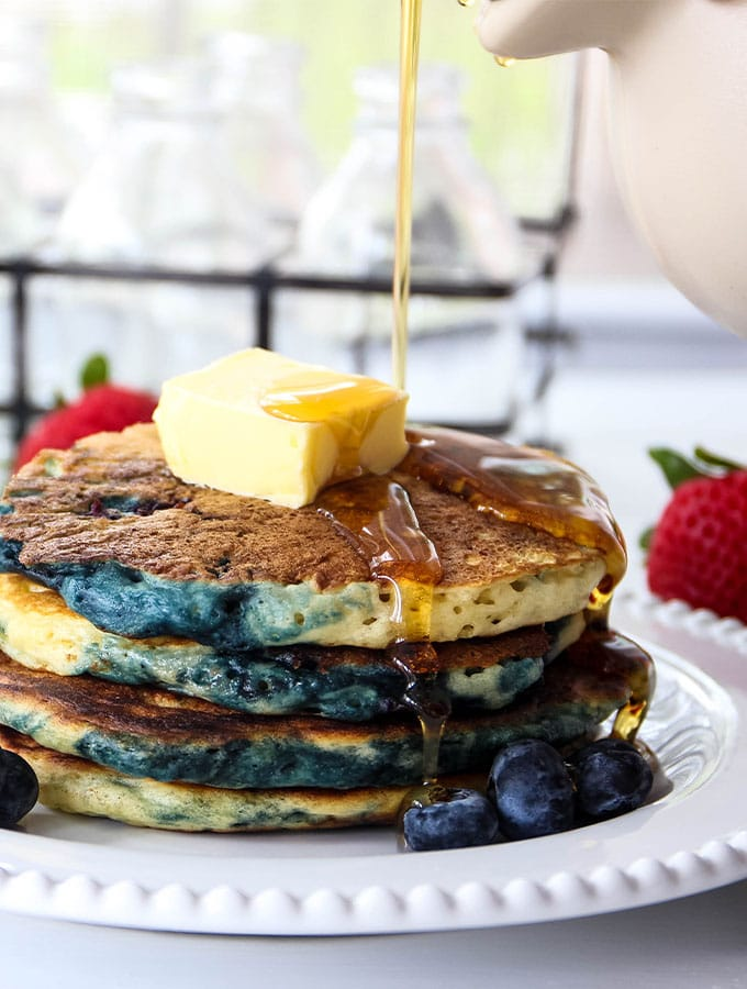 Buttermilk pancakes are stacked and topped with butter and maple syup.