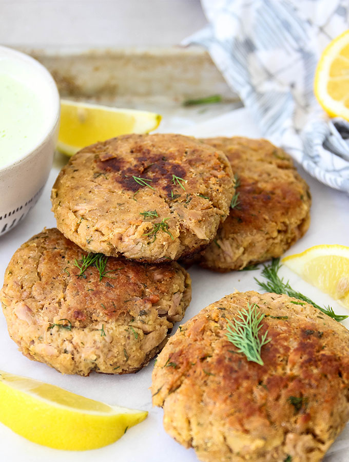 Tuna patties are stacked and topped with fresh dill and lemon wedges.