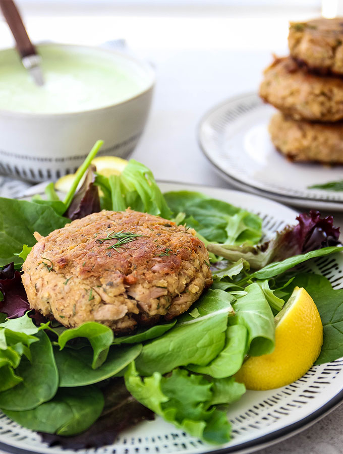 Tuna patties are plated with a fresh lemon wedge and salad, then topped with dill sauce.