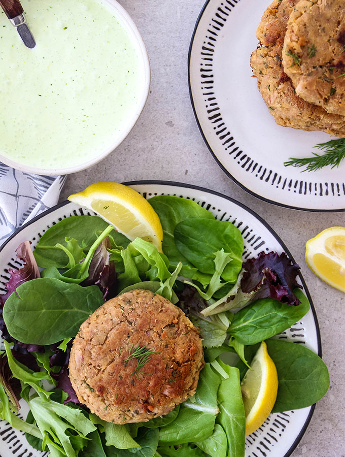 A tuna patty is plated over salad with a bowl of dressing and more patties nearby.