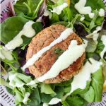 A tuna patty is plated over fresh salad and topped with a lemon wedge and dill sauce.