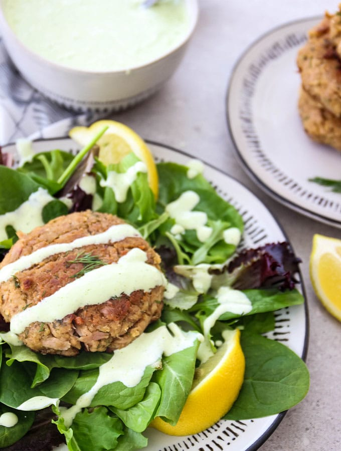 Tuna patties are plated over fresh salad and topped with dill sauce.