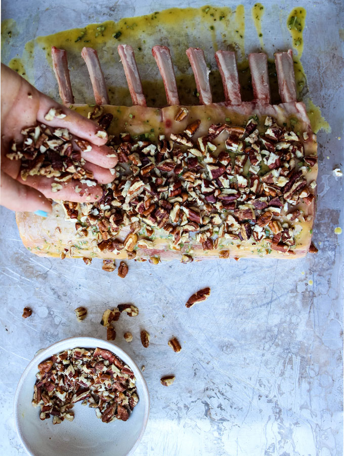 Pecans are crushed and placed on the rack of lamb.