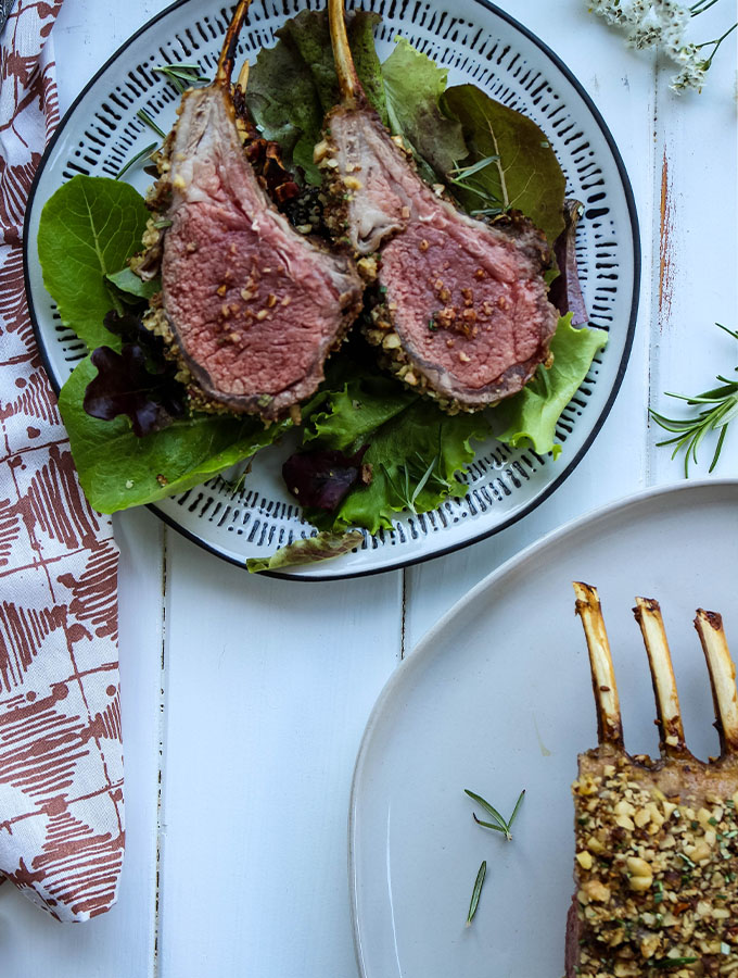 The rack of lamb is sliced abnd displayed to show the medium rare doneness.